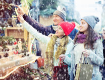 Friendly family couple with teen girl choosing Christmas decorat. Ion at fair Stock Image