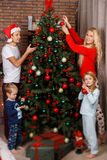 Friendly family decorates Christmas pine Royalty Free Stock Photo