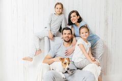 Friendly family of four memebers: cheerful European brunette fem. Ale, her husband, two daughters and favourite pet, have good relationships, support each other stock photos