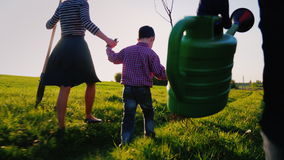 A friendly family is going to plant a tree. Rear view, in the foreground of the watering can. A little boy is running stock video footage