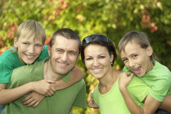Friendly family in green shirts. Walking in the summer park stock images