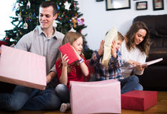 Friendly family members presenting gifts on Christmas. At home. Focus on men and girl Royalty Free Stock Photos