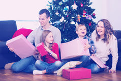 Friendly family members presenting gifts on Christmas. At home. Focus on men and girl Royalty Free Stock Images