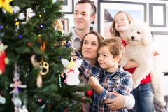 Friendly family members presenting gifts on Christmas. At home. Focus on men and girl Royalty Free Stock Photography