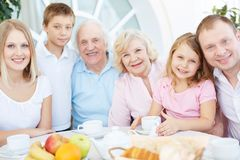 Friendly family. Portrait of senior and young couples with their children having dinner at home Royalty Free Stock Image
