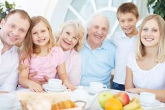 Friendly family. Portrait of senior and young couples with their children having dinner at home Royalty Free Stock Images