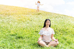 Friendly family relaxing on meadow. Full length portrait of calm women meditating on grassland with closed eyes. Her daughter is running to her on background Royalty Free Stock Images