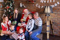 Large family together with Santa Claus gathered on eve of Christ. Friendly family and Santa Claus show that everything good in cozy spacious room decorated for Stock Photo