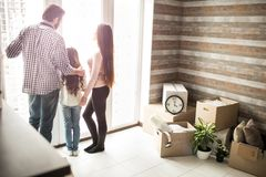 Friendly family is standing near window and looking outside. There are man boxes on the right side of apartment. People royalty free stock photography