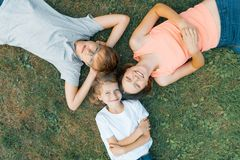 Friendly family of three children having fun on the green grass, top view for 3 children royalty free stock photography