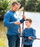 Friendly father and son fishing with rods. In summer day Stock Images