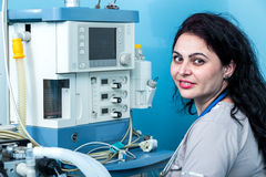 Friendly female anesthesiologist portrait in the operating room. Young female anesthesiologist doctor in front of a ventilator machine preparing for surgery Royalty Free Stock Photos
