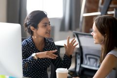 Friendly female colleagues are having pleasant conversation. Friendly female colleagues having good relationships, pleasant conversation at workplace during stock image