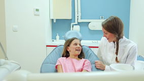 Friendly female dentist talking with cute girl before routine check up stock video