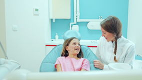 Friendly female dentist talking with cute girl before routine check up stock video footage