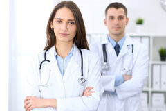 Friendly female doctor on the background of a male physician in hospital office. Ready to examine and help patients. High level and quality medical service Royalty Free Stock Images