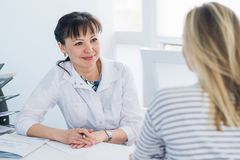 Friendly female doctor comforting middle aged patient in hospital.  Stock Photos