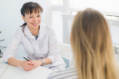 Friendly female doctor comforting middle aged patient in hospital.  Stock Image