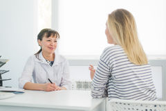 Friendly female doctor comforting middle aged patient in hospital.  Royalty Free Stock Image