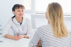 Friendly female doctor comforting middle aged patient in hospital.  Royalty Free Stock Photos