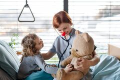 Friendly female doctor examining small girl in bed in hospital. Friendly female doctor with stethoscope examining small girl in bed in hospital