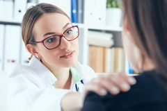 Friendly female doctor in glasses touching patient shoulder. Encouragement, empathy, cheering and support after medical. Friendly female doctor touching patient royalty free stock photos