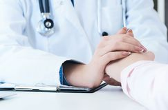 Friendly female doctor hands holding patient hand sitting at the desk for encouragement, empathy, cheering and support. While medical examination. Bad news royalty free stock photo