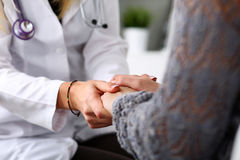 Friendly female doctor hold patient hand in office during recept Royalty Free Stock Photos