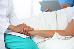 Friendly female doctor's hands holding patient's hand Stock Image