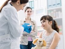 Friendly doctor showing a syringe to a girl before giving the injection royalty free stock photos