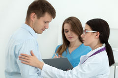 Friendly female doctor touching male patient's arm for empathy Stock Photo