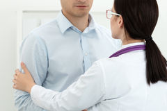 Friendly female doctor touching male patient's arm for empathy Stock Image