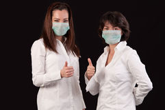 Friendly female doctors with thumbs up over black Royalty Free Stock Photography
