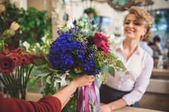 Friendly female florist giving bouquet to client Royalty Free Stock Image