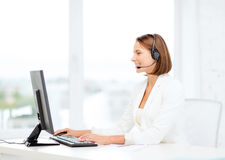 Friendly female helpline operator with computer Royalty Free Stock Photography