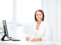 Friendly female helpline operator with computer Stock Image