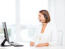 Friendly female helpline operator with computer Stock Photo