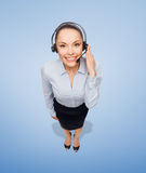 Friendly female helpline operator with headphones Stock Photography