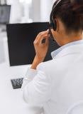 Friendly female helpline operator with headphones Stock Photo