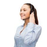 Friendly female helpline operator with headphones Stock Image