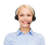 Friendly female helpline operator with headphones. Business and office concept - friendly female helpline operator with headphones Royalty Free Stock Images