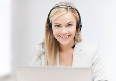 Friendly female helpline operator with laptop Stock Image