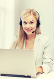 Friendly female helpline operator with laptop Royalty Free Stock Photo