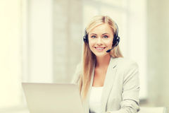 Friendly female helpline operator with laptop Stock Photo