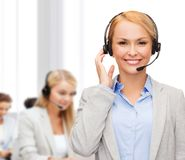 Friendly female helpline operator at office. Business, technology and call center concept - friendly female helpline operator with headphones at office Stock Photography