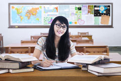 Friendly female high school student studying in class. Portrait of beautiful high school student with long hair, studying in the classroom and smiling at the stock images