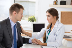 Friendly female medicine doctor's holding male patient's hand su Royalty Free Stock Photo