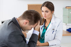 Friendly female medicine doctor's holding male patient's hand su. Pporting him. Bad news, stress and depression concept Stock Photo