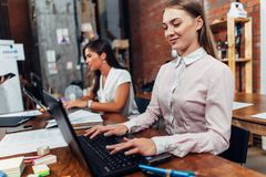 Friendly female office workers wearing formal workwear typing on laptop keyboard working in creative agency.  royalty free stock photography