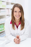 Friendly female pharmacist leaning on the counter Royalty Free Stock Images